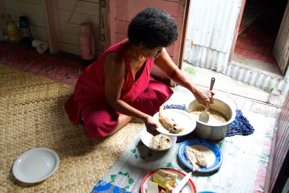 Wife of our host serving a lunch of fresh fish stewed in coconut